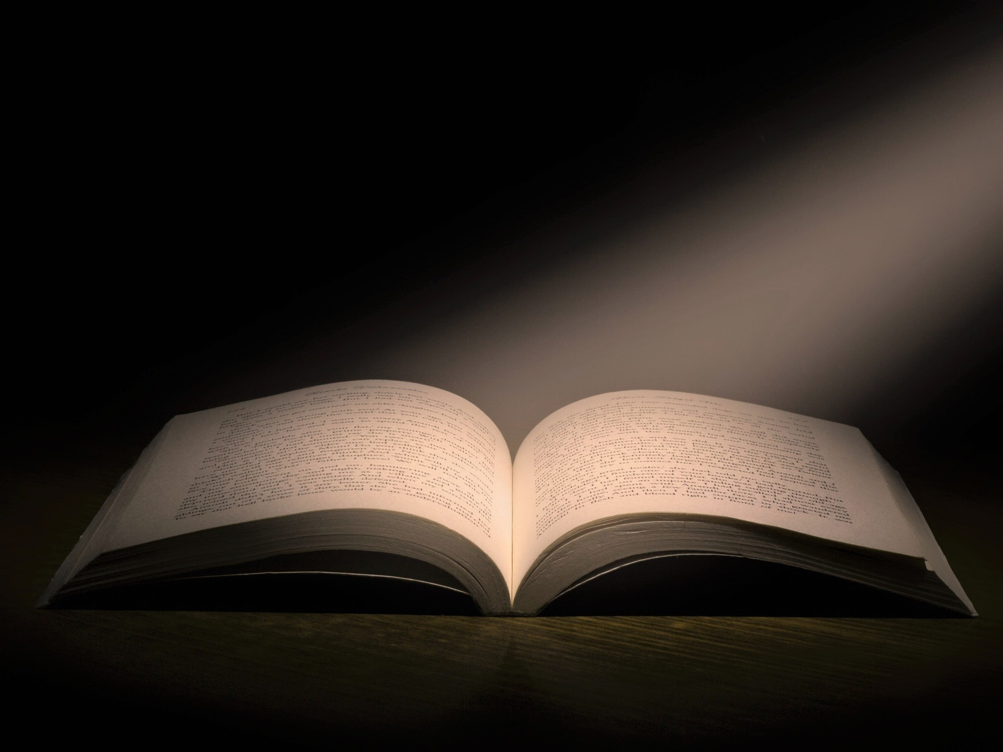 Open pages of a large book highlighted  by a shaft of light representing wisdom, knowledge, learning, and enlightenment.