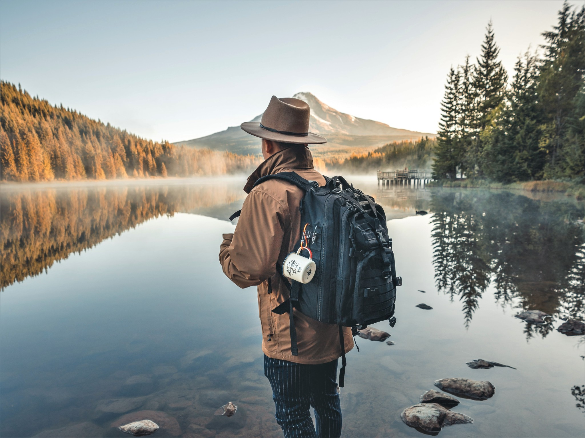 Male explorer and adventurer looking out over lake, forest, and mountain scenery.