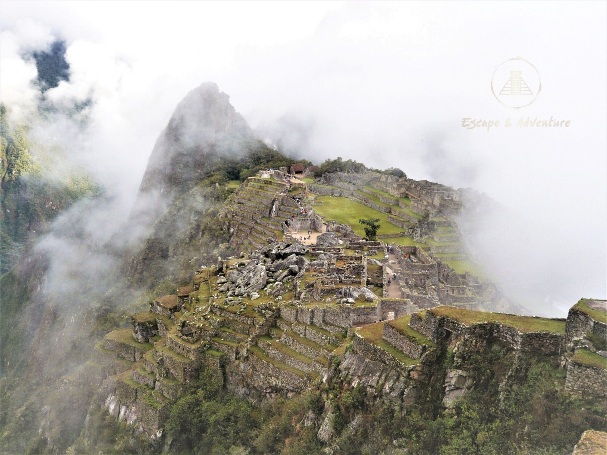 View of Machu Picchu ruins partly obscured by atmospheric clouds.