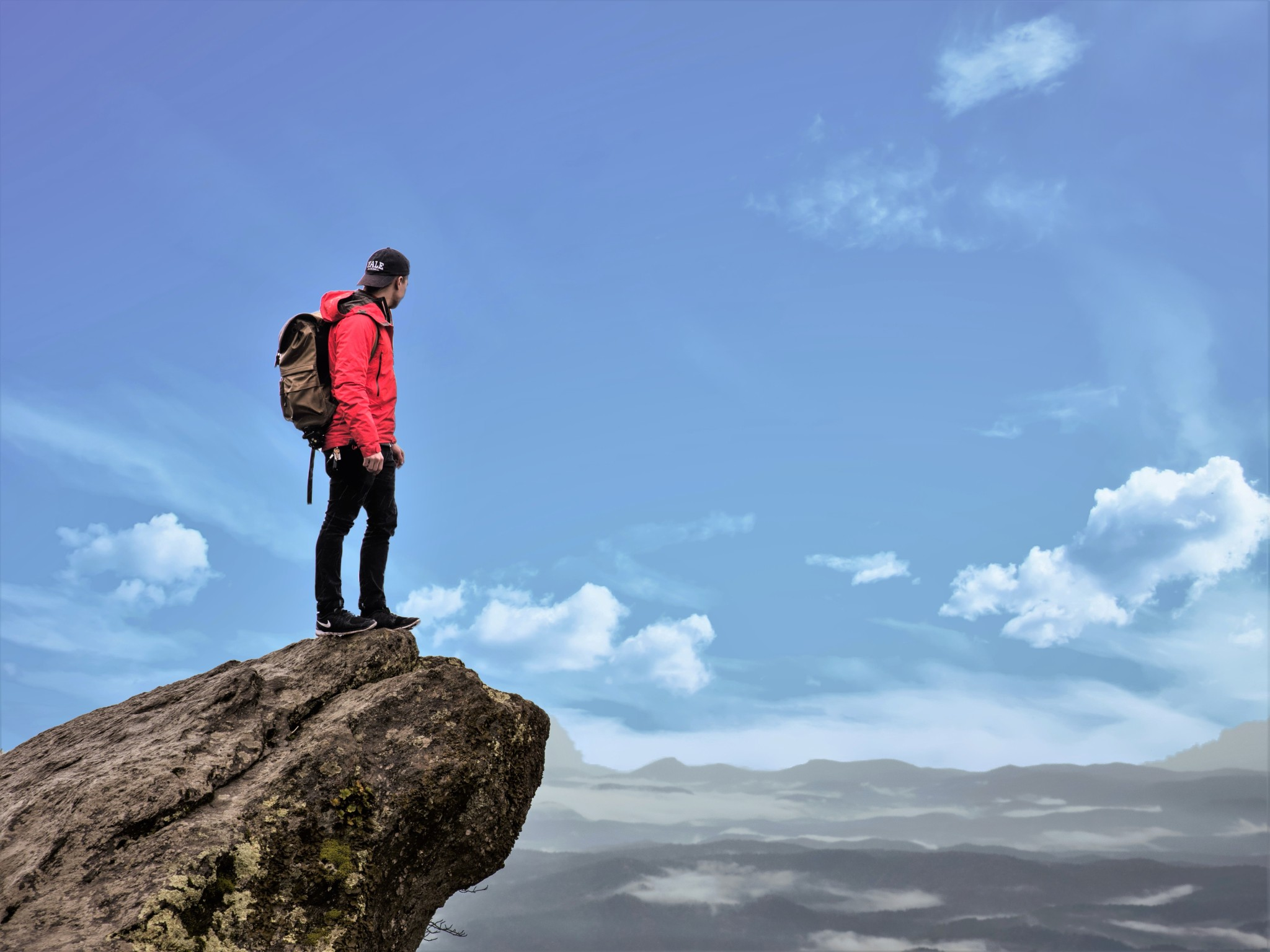 Male hiker standing on the precipice of a chasm contemplating his future.