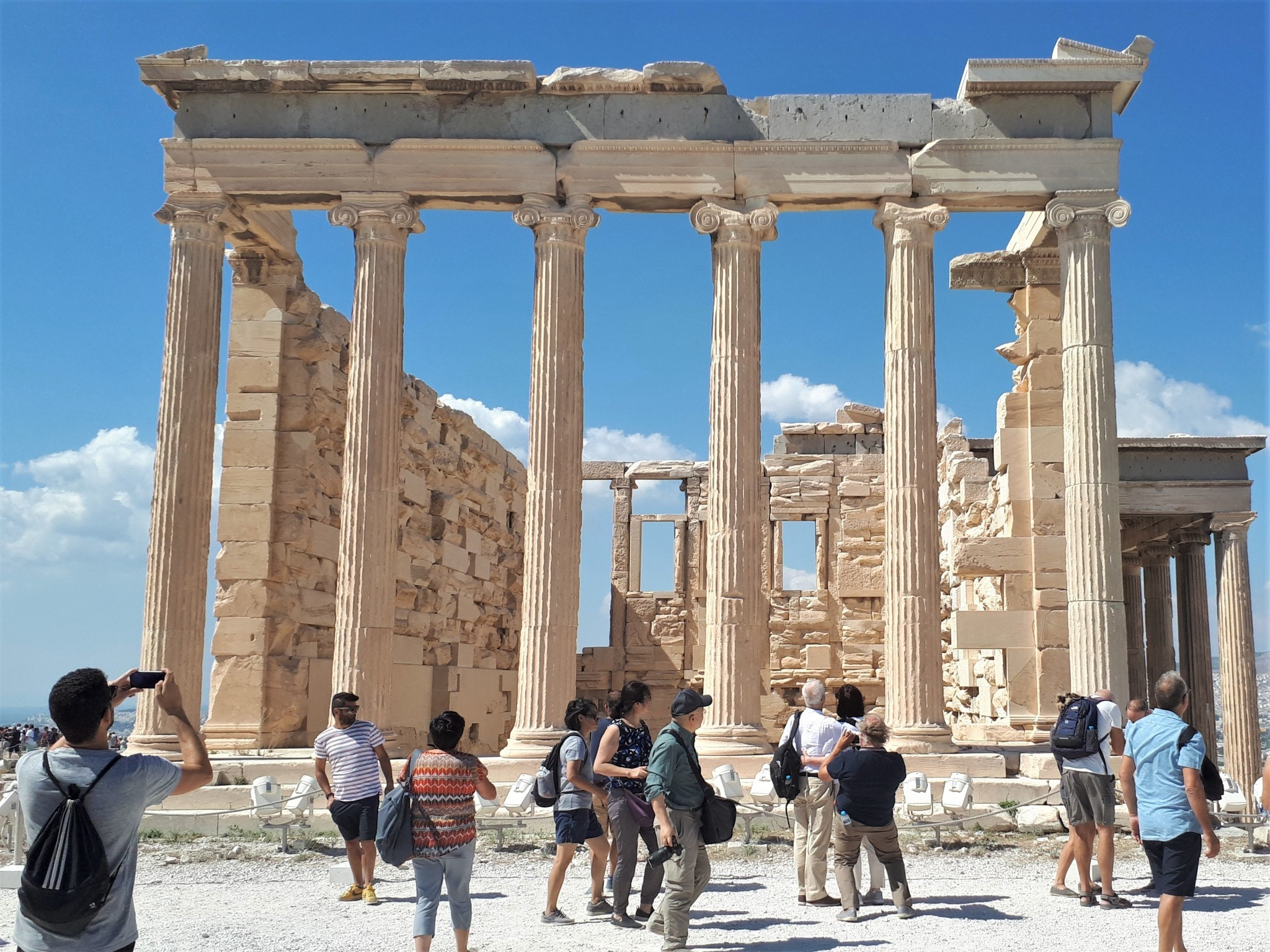 A crowd of tourists spoiling the peaceful atmosphere of an ancient Greek columned ruin.