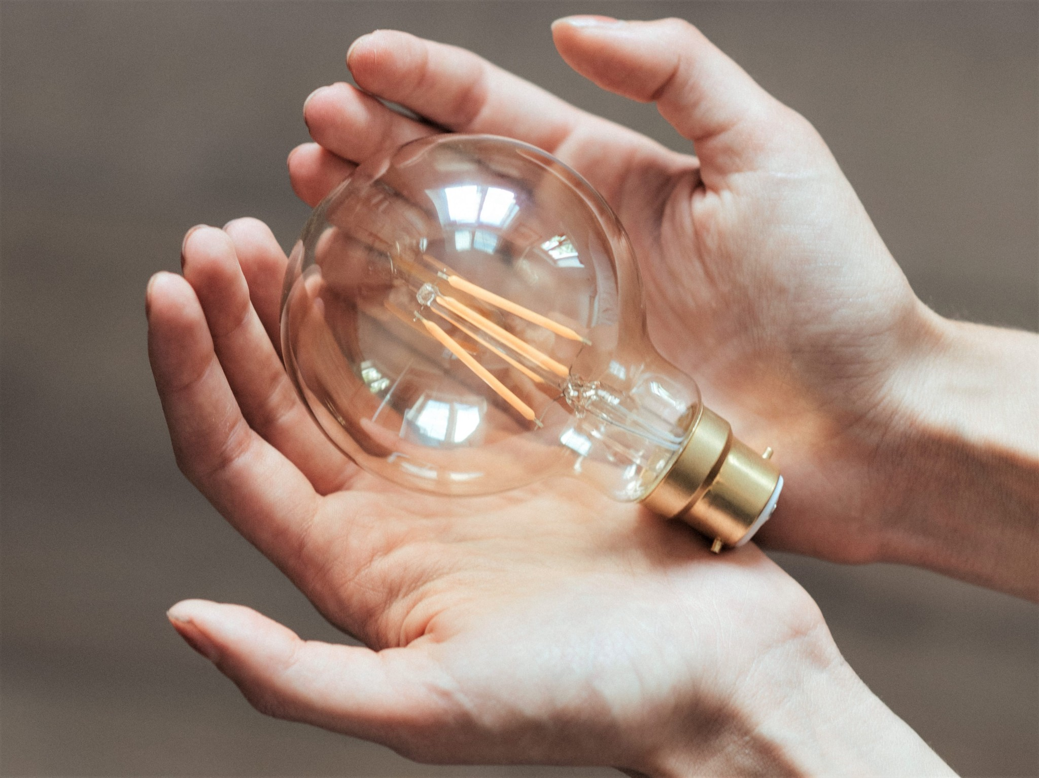 Woman holding a lightbulb in the palms of her hands, representing, natural resource protection, energy saving, sustainability, and responsible tourism.
