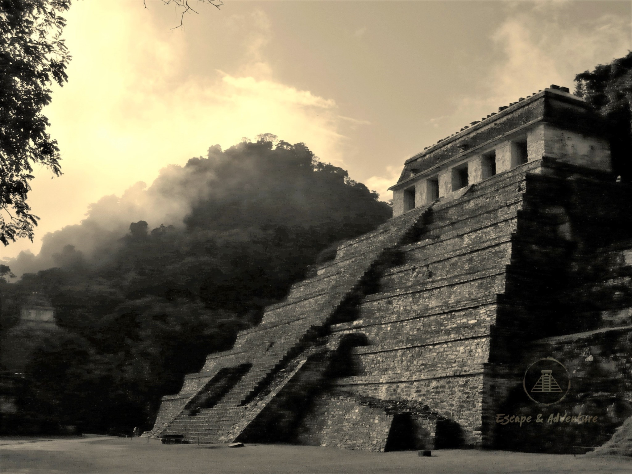 Atmospheric ruined Mayan pyramid at Palenque, Mexico set against a background of misty jungle.