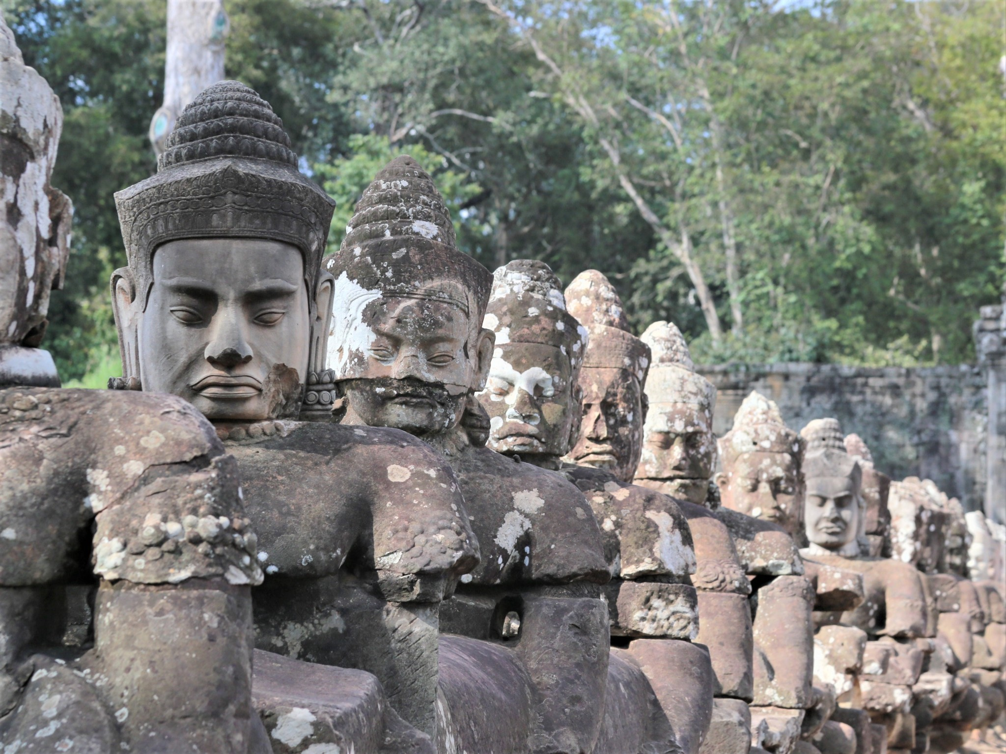 A row of stone statues with sombre facial expressions at Angkor, Cambodia.