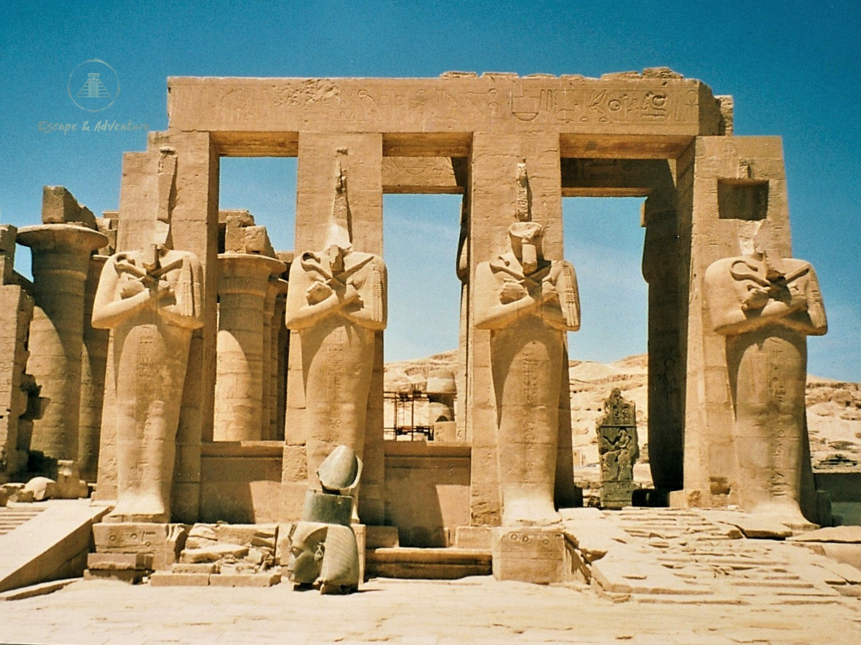 Four headless Ancient Egyptian statues set against a vivid blue sky at The Ramesseum, Theban Necropolis, Egypt.