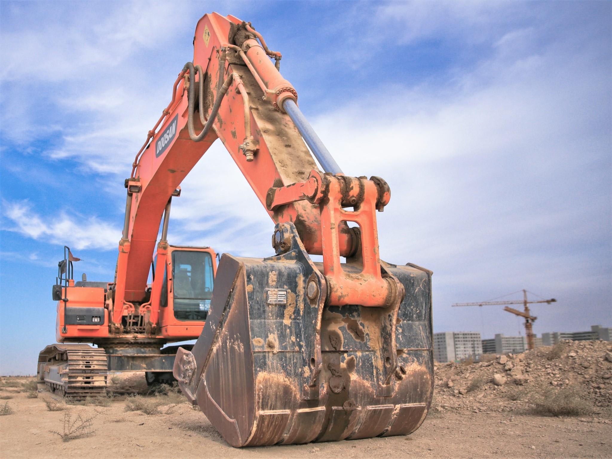 A large orange mechanical digger excavating a construction site for urban development.