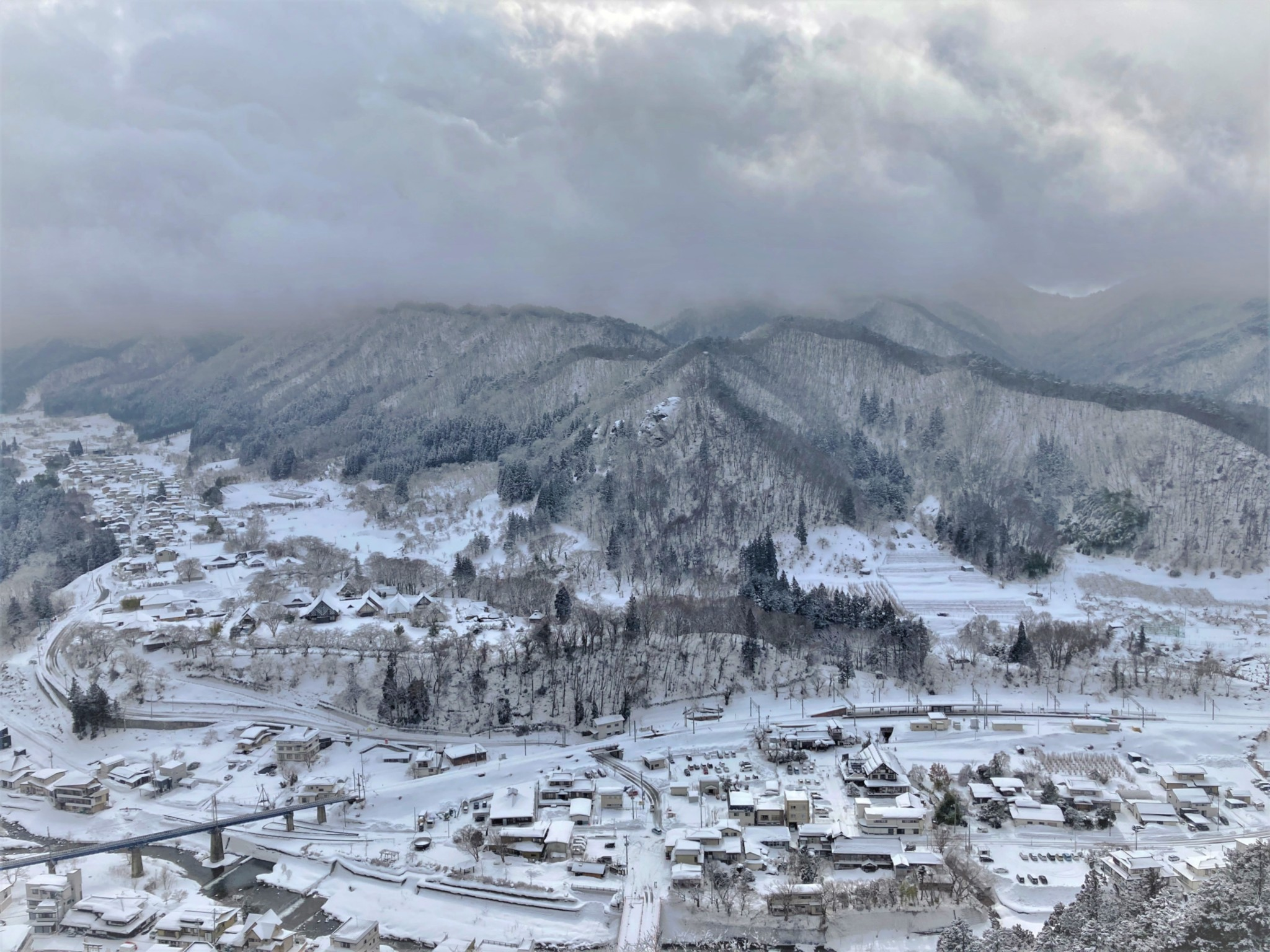 A winter view of the Japanese town of Yamadera covered in snow, situated in front of barren mountains on a cloudy day.