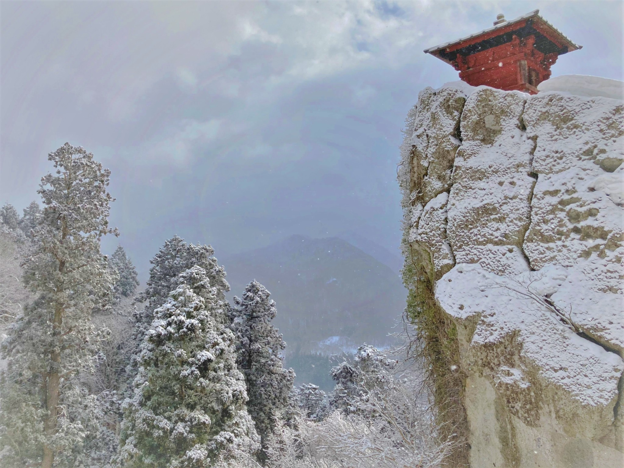 A winter view of a red wooden sutra repository perched on the edge of a cracked and icy cliff at Risshaku-ji in Yamadera, Japan.