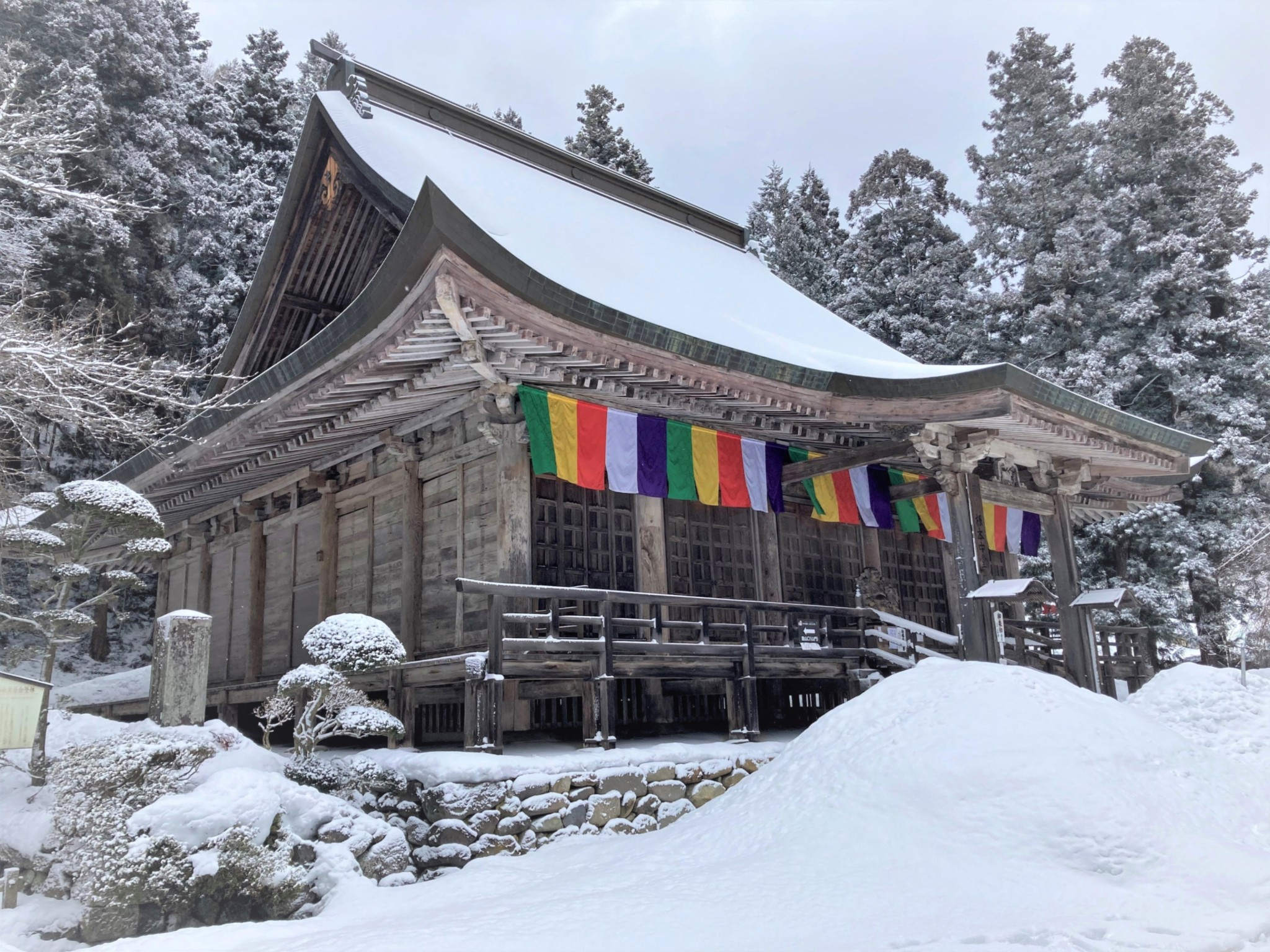 A large ornate Japanese Buddhist temple situated in front of a snowy forest.