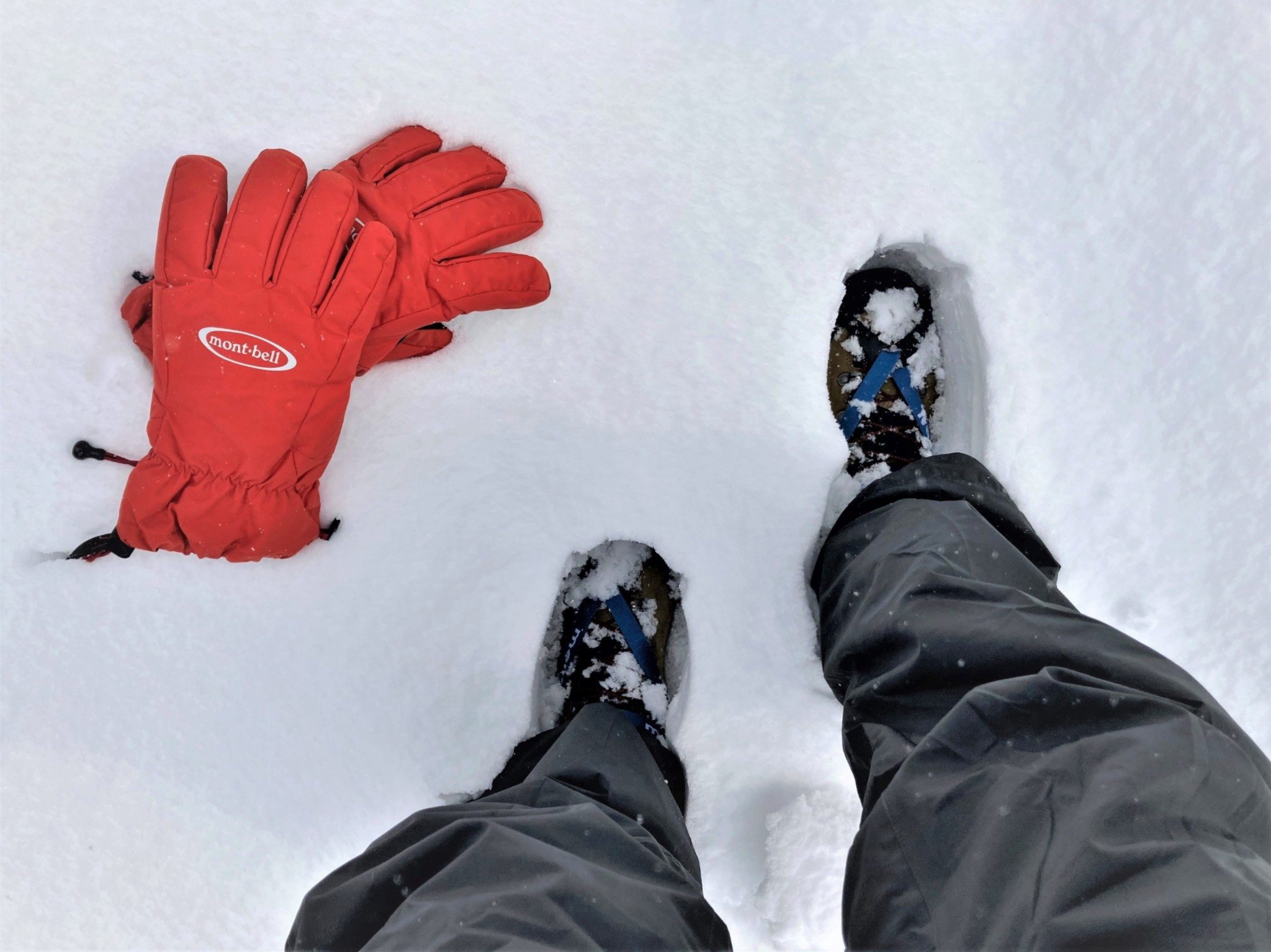 A man walking through deep snow with crampons and bright red gloves.