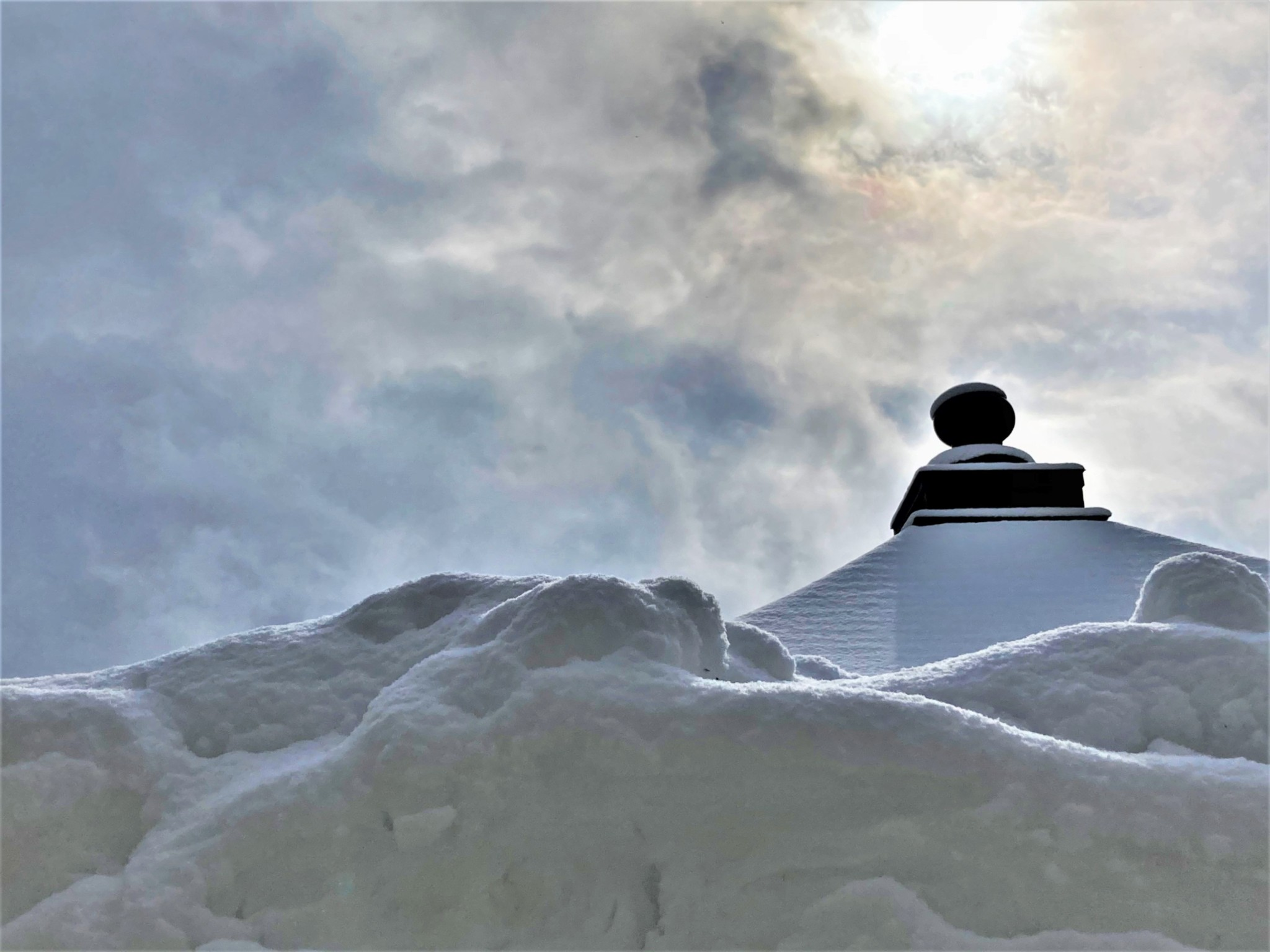 The winter sun piercing the clouds over the roof of a Japanese Buddhist temple and a large bank of snow.
