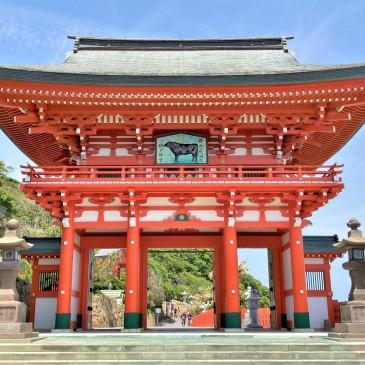 The large vermillion entrance gate of Udo Shrine in Miyazaki Japan, set against a blue sky.