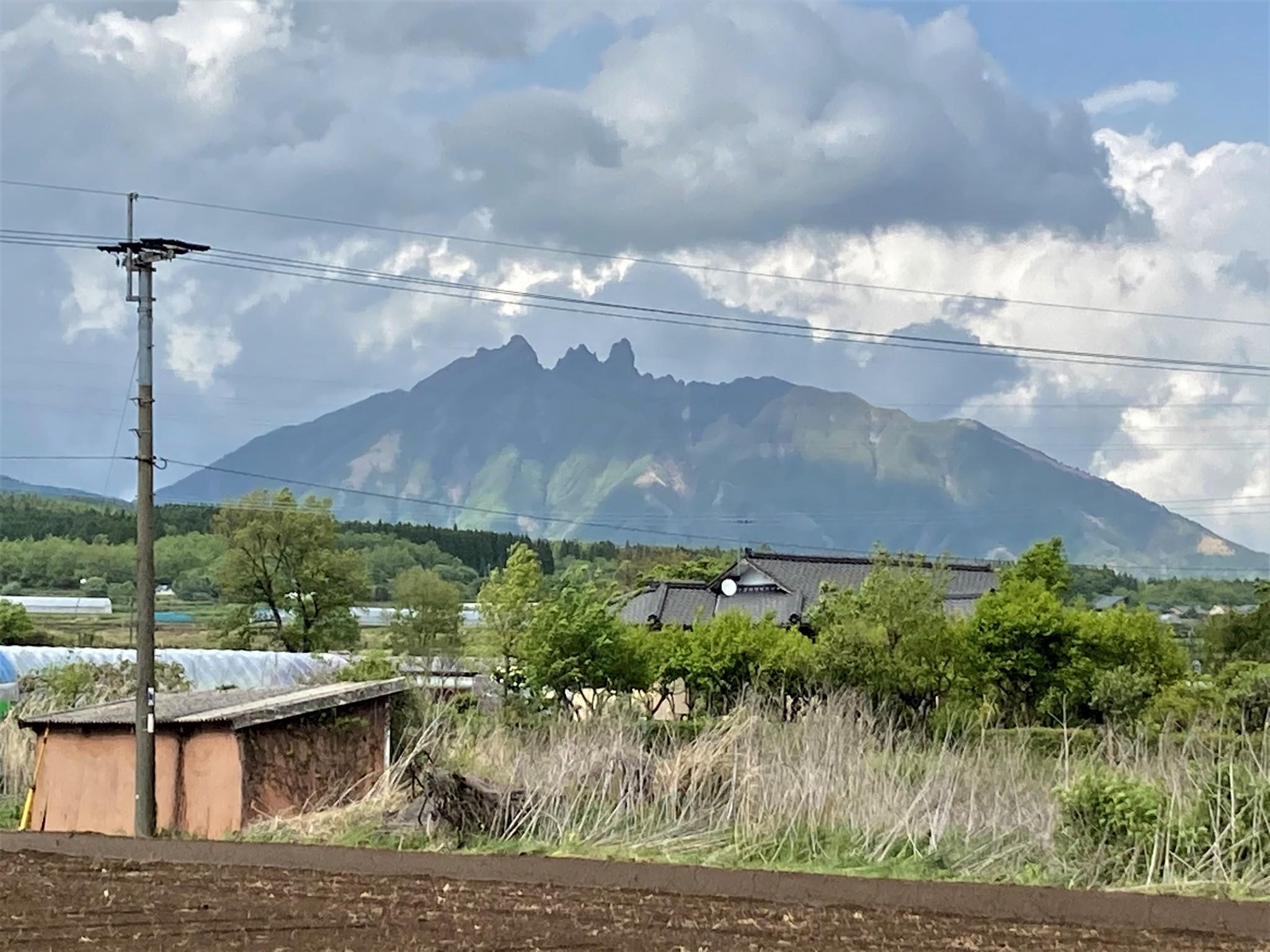 A rugged volcanic peak rising above farmland in Aso, Kyushu.