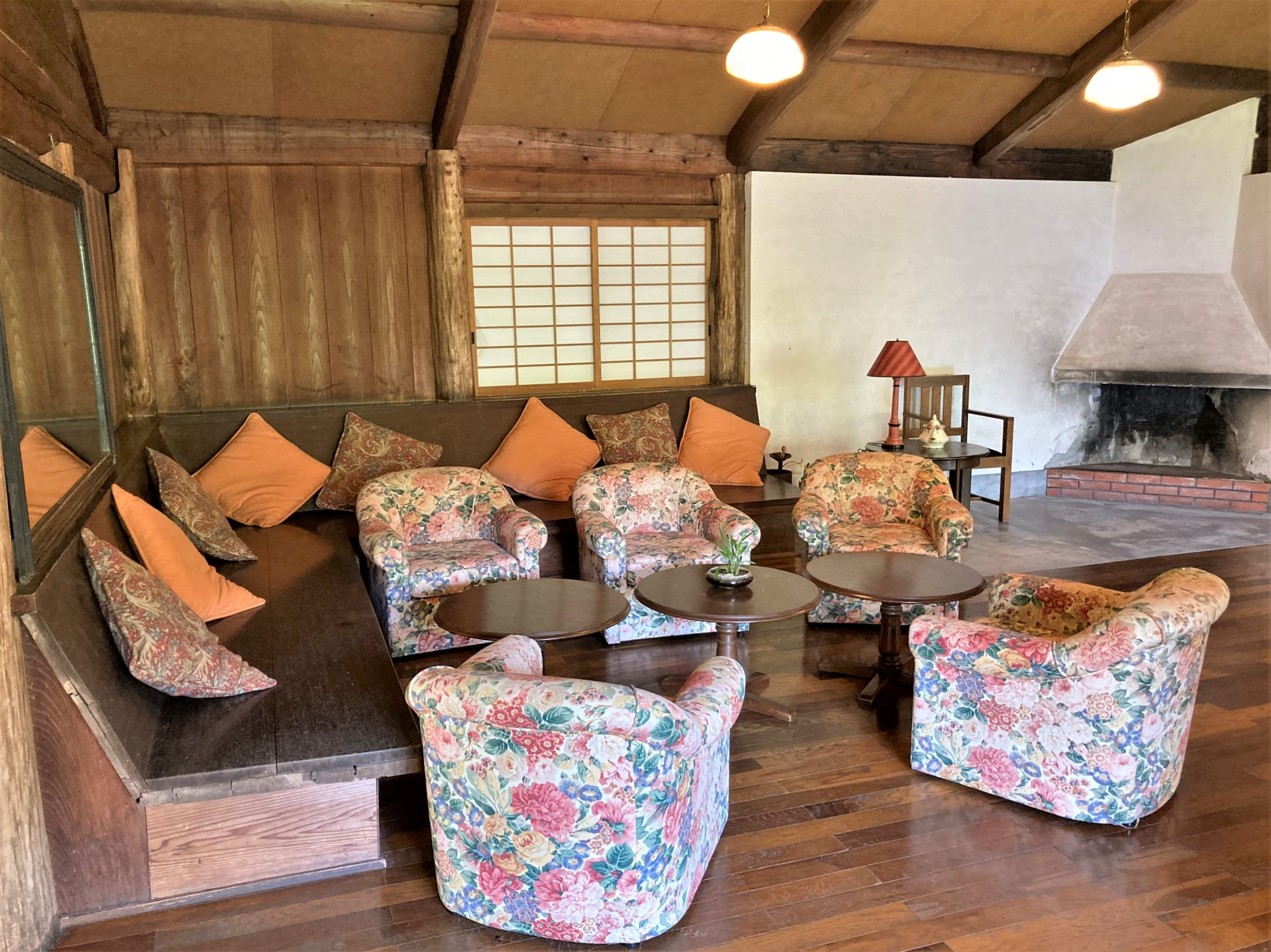 The lounge of the Eikokukan clubhouse in Hinokage, Japan decorated with flower-patterned chairs, wooden benches and a traditional fireplace.