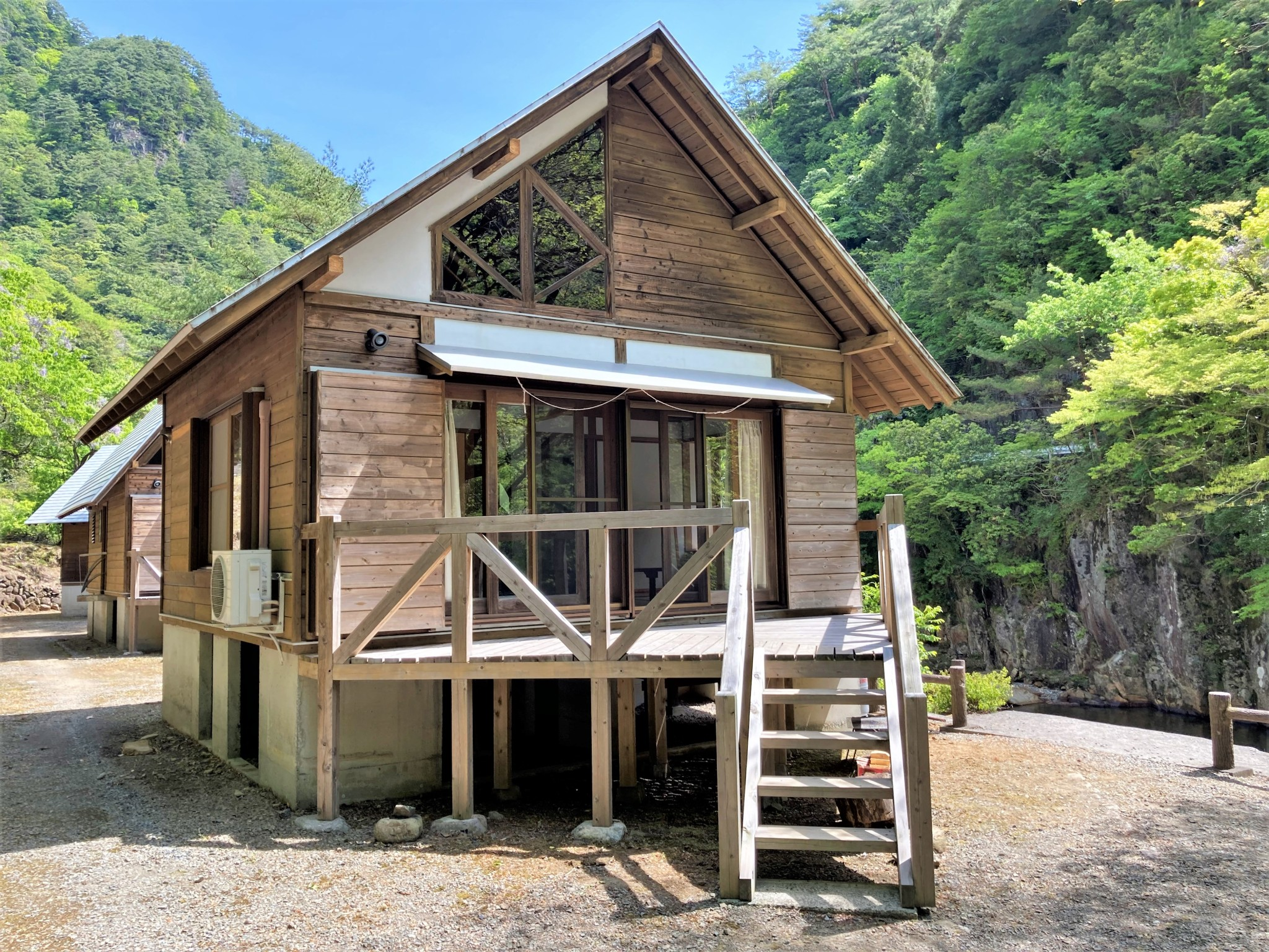 Wooden rental cabins in the Mitate Valley, Kyushu set against a blue sky and verdant woodland.