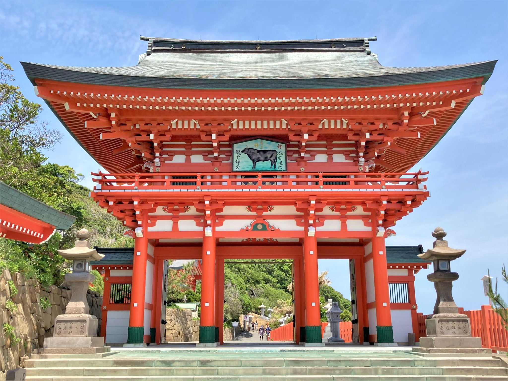 A bright red torii gate set against blue sky at the entrance of Udo Shrine in Miyazaki, Japan.