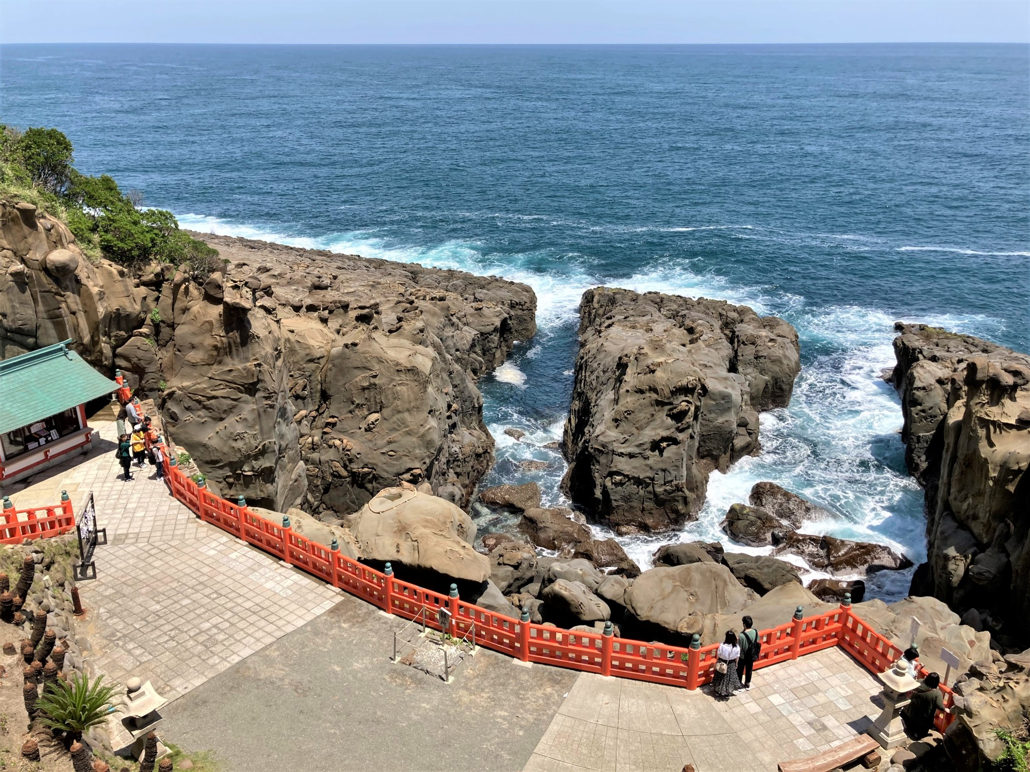 Two small groups of tourists looking out over the rocky headland and ocean at Udo Shrine in Miyazaki, Japan.