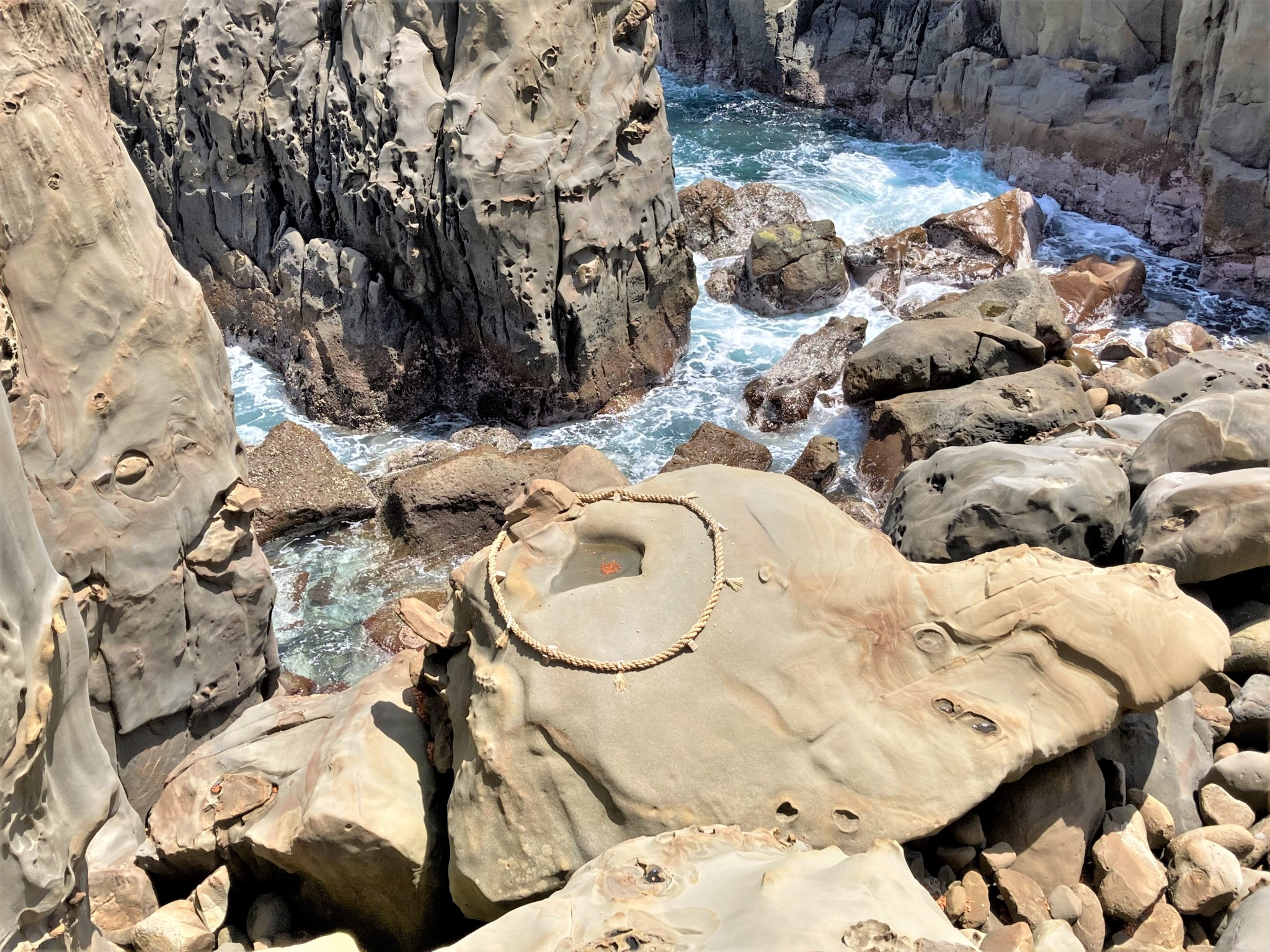 Ocean-side cliffs and a giant boulder at Udo Shrine, Miyazaki decorated with a large circle of rope that designates a sacred place in Japan's Shinto religion.