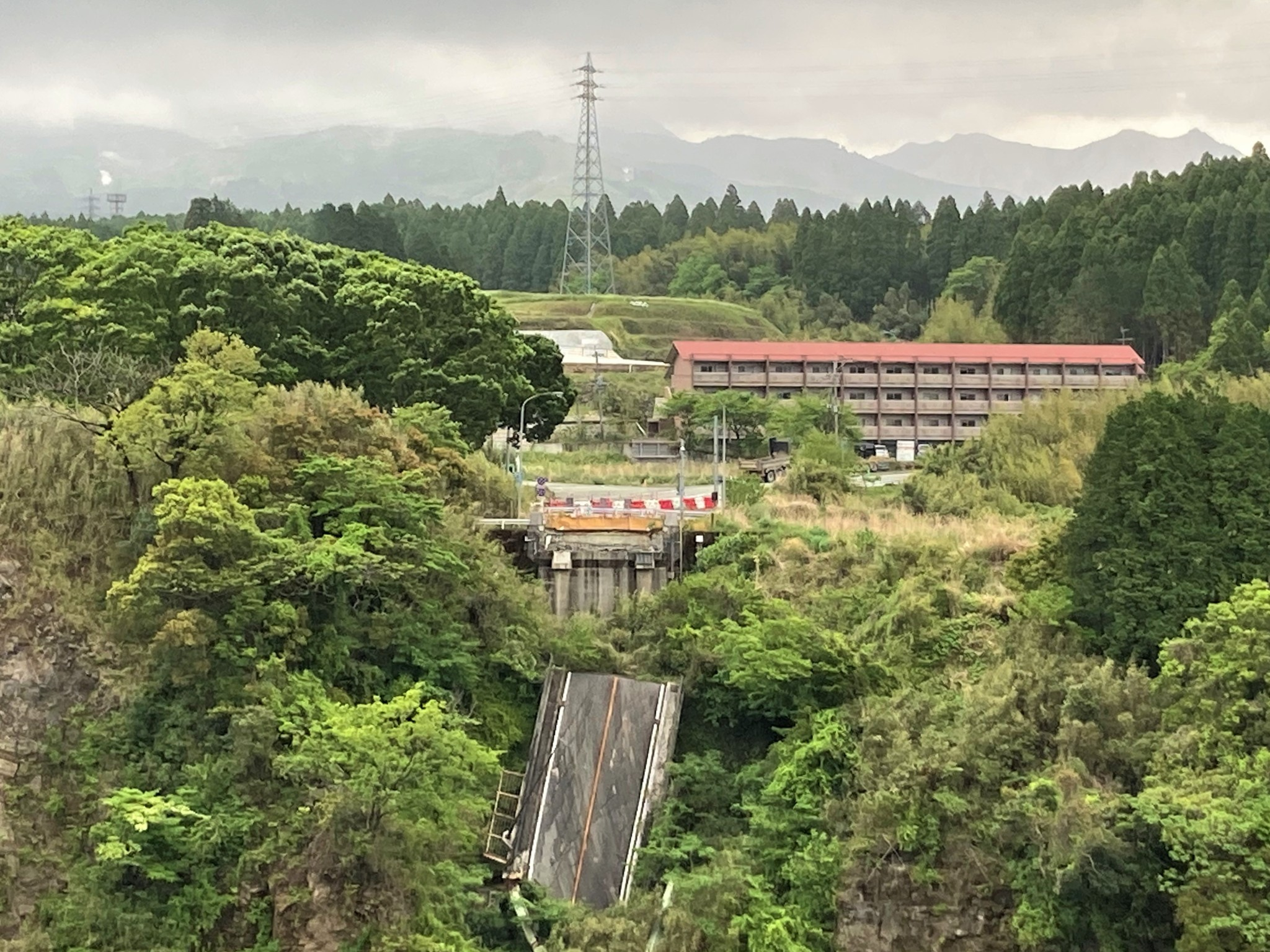 The remains of a concrete bridge destroyed during the 2016 Kumamoto earthquake hanging over the side of a tree-covered ravine.