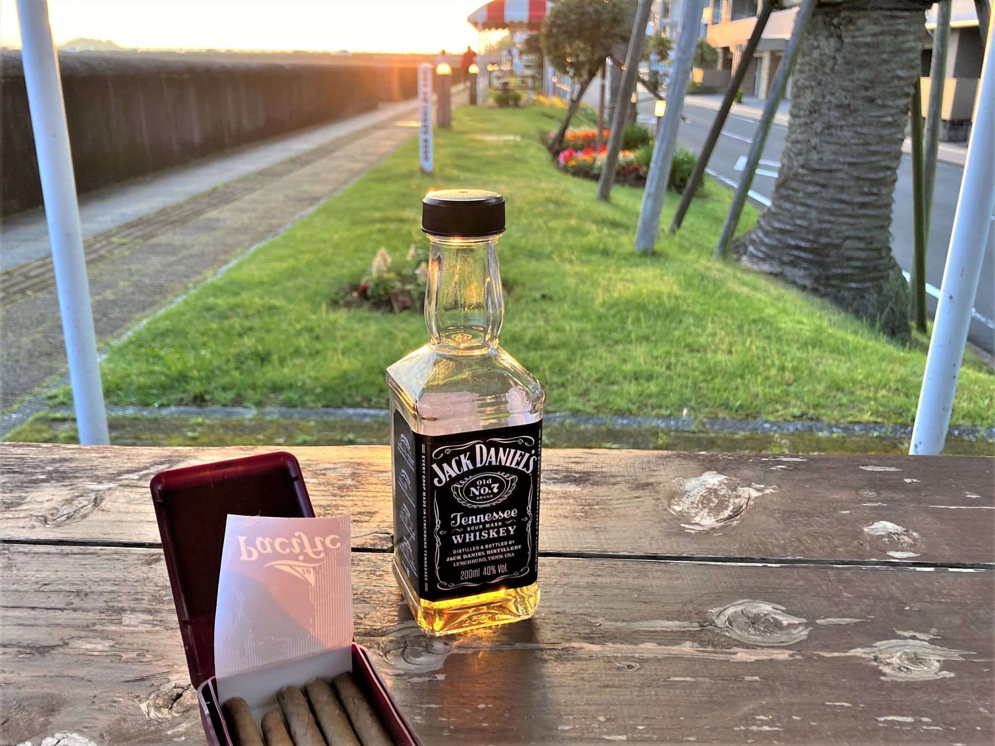 A bottle of whisky and packet of cigars on a wooden table in front of green grass at sunset.