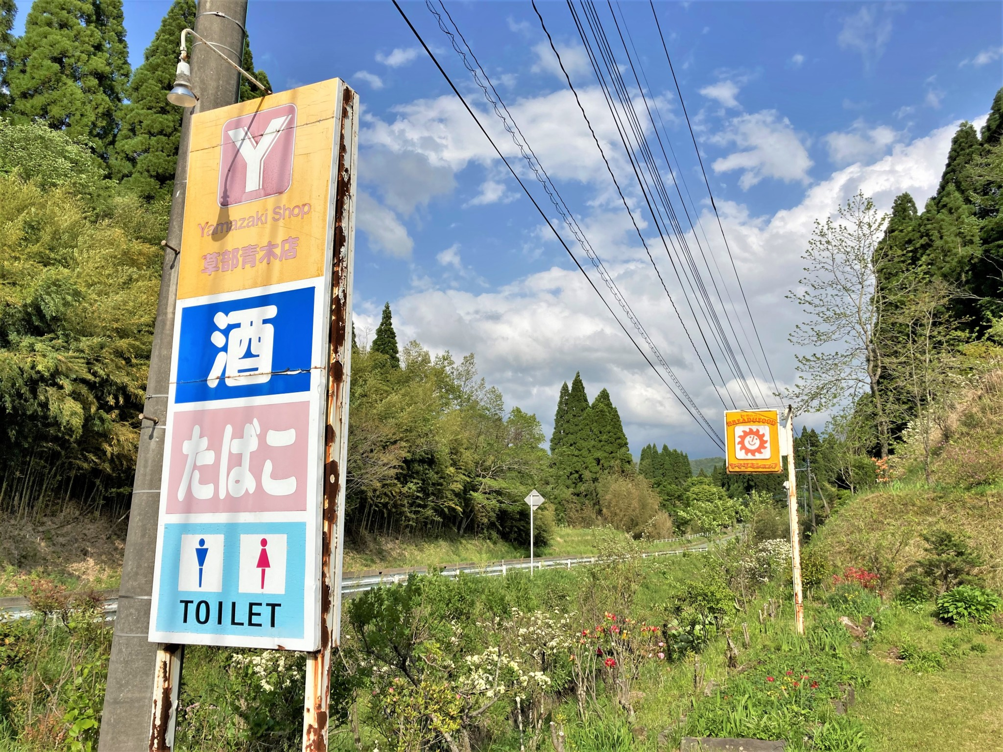 A roadside convenience store sign set against blue sky along a verdant country road leading to Aso, Kyushu.