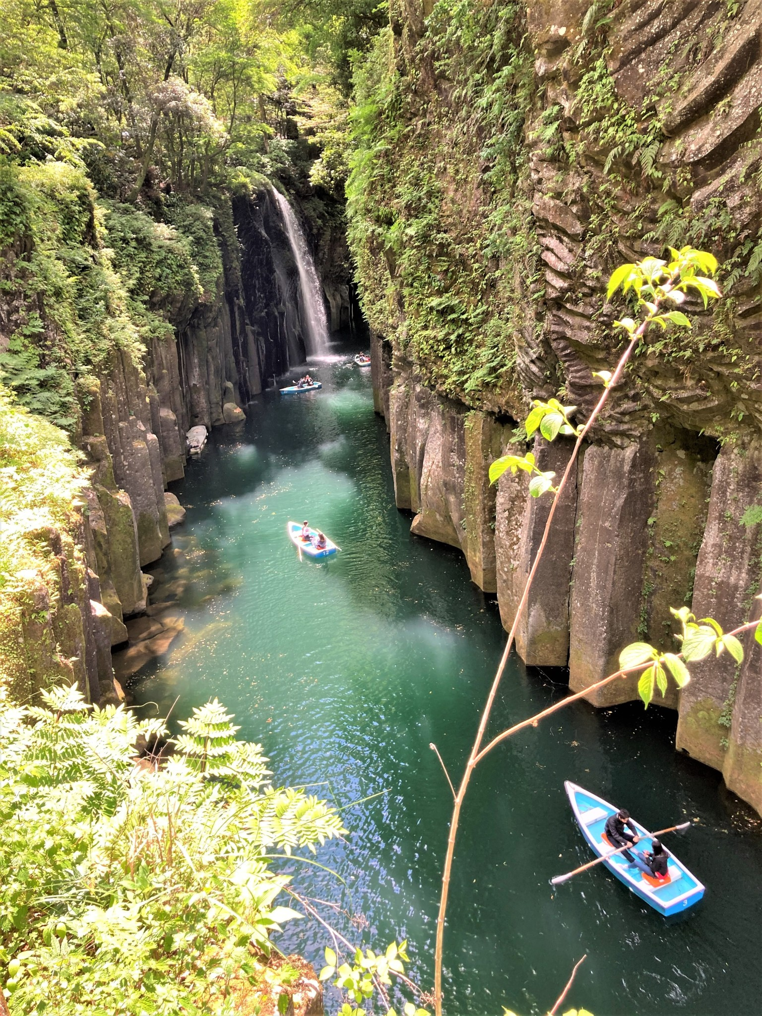 Two couples in rowing boats enjoying the waterfalls and scenery of Takachiho Gorge in Miyazaki, Japan.