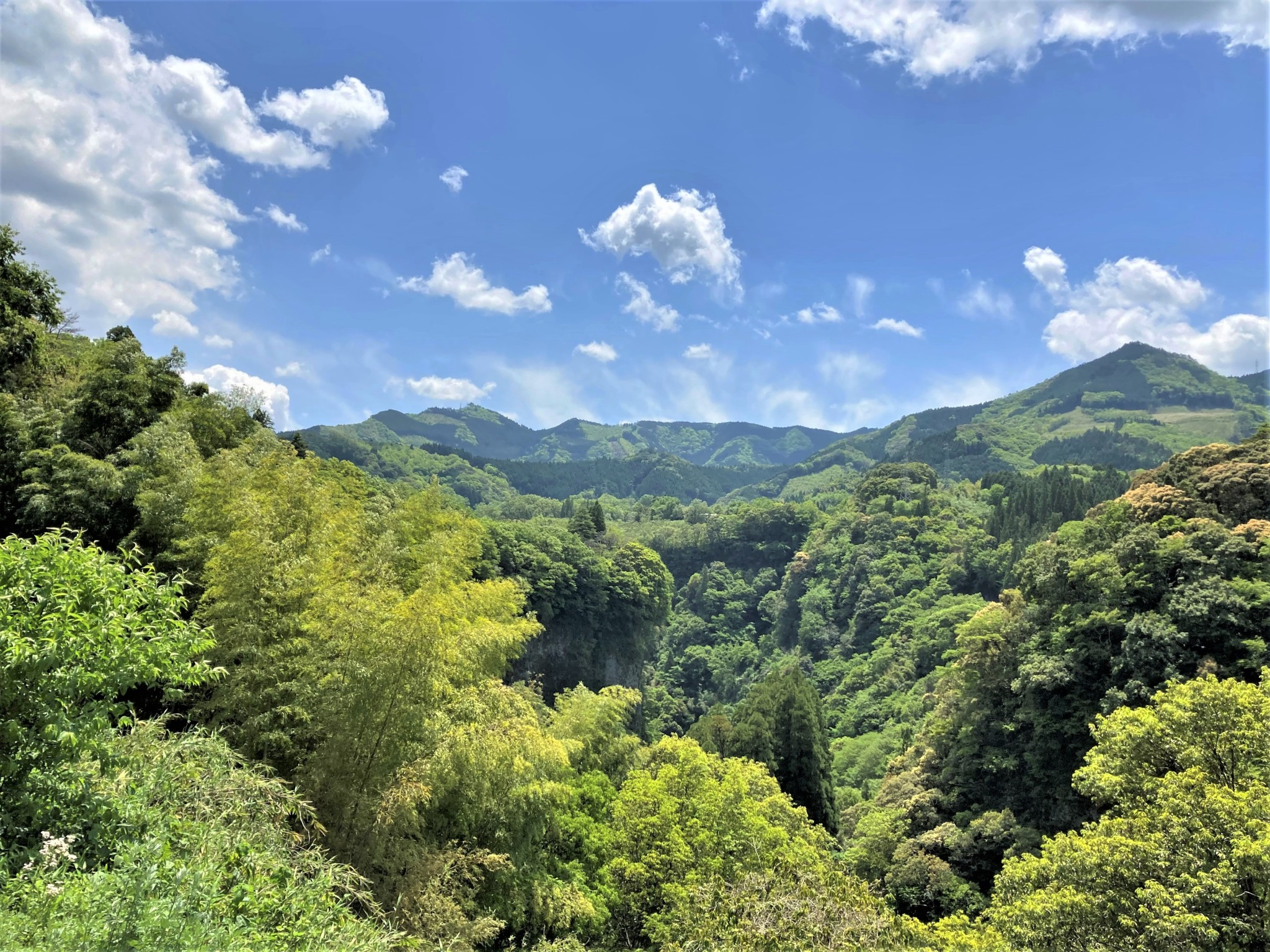 The green hills and valleys of Kyushu, Japan beneath a bright blue and partially cloudy sky.