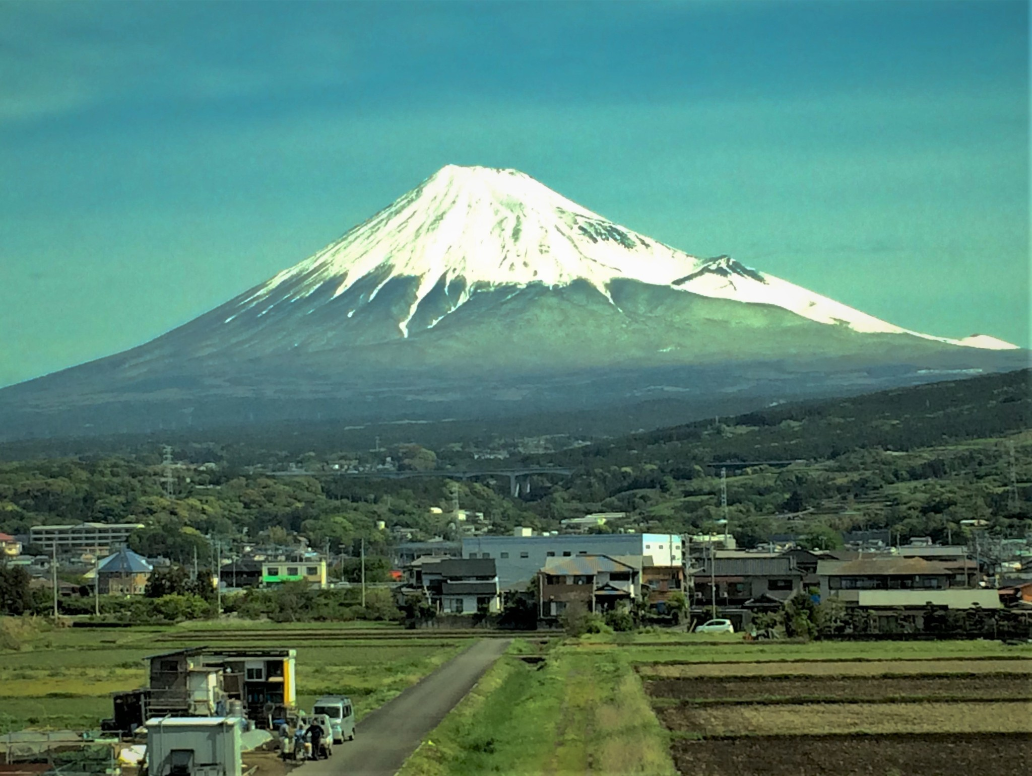 The imposing profile of a snow-covered Mount Fuji rising from the surrounding green plains to dominate the Japanese landscape.