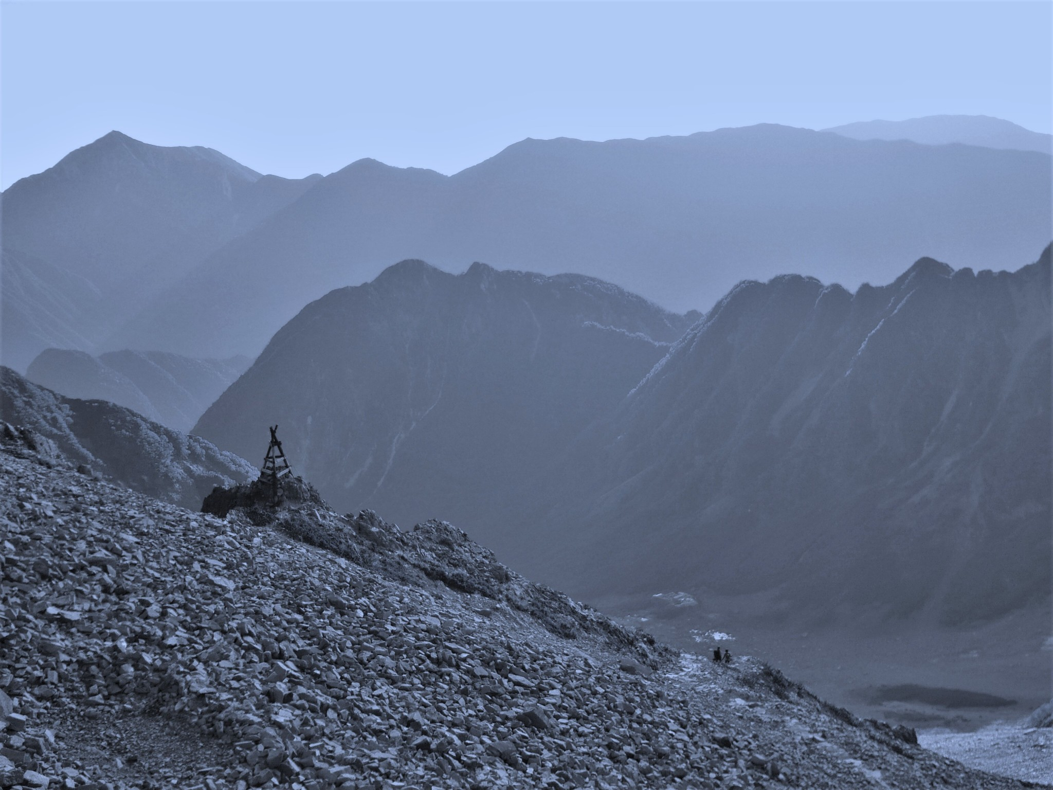 A panoramic blue-hued view of a jagged mountain ridgeline and descending slopes in the Japan Alps.