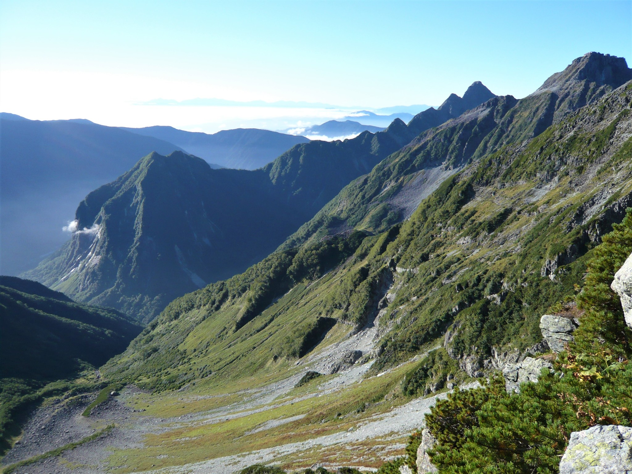 A panoramic view of a jagged mountain  ridgeline and green valley in the Japan Alps.