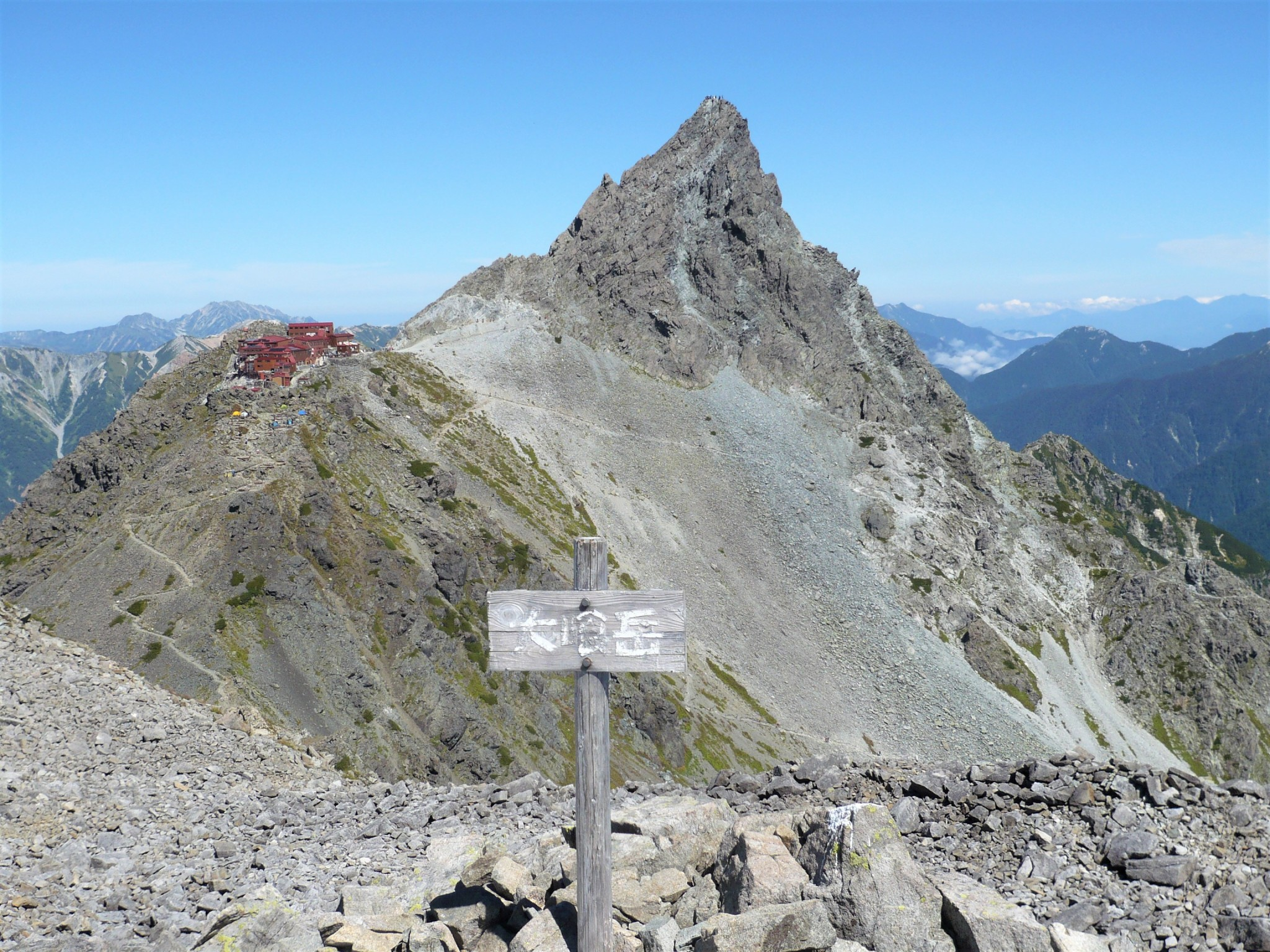 The spear-shaped summit of Mount Yari in Japan shooting upwards towards the blue sky.