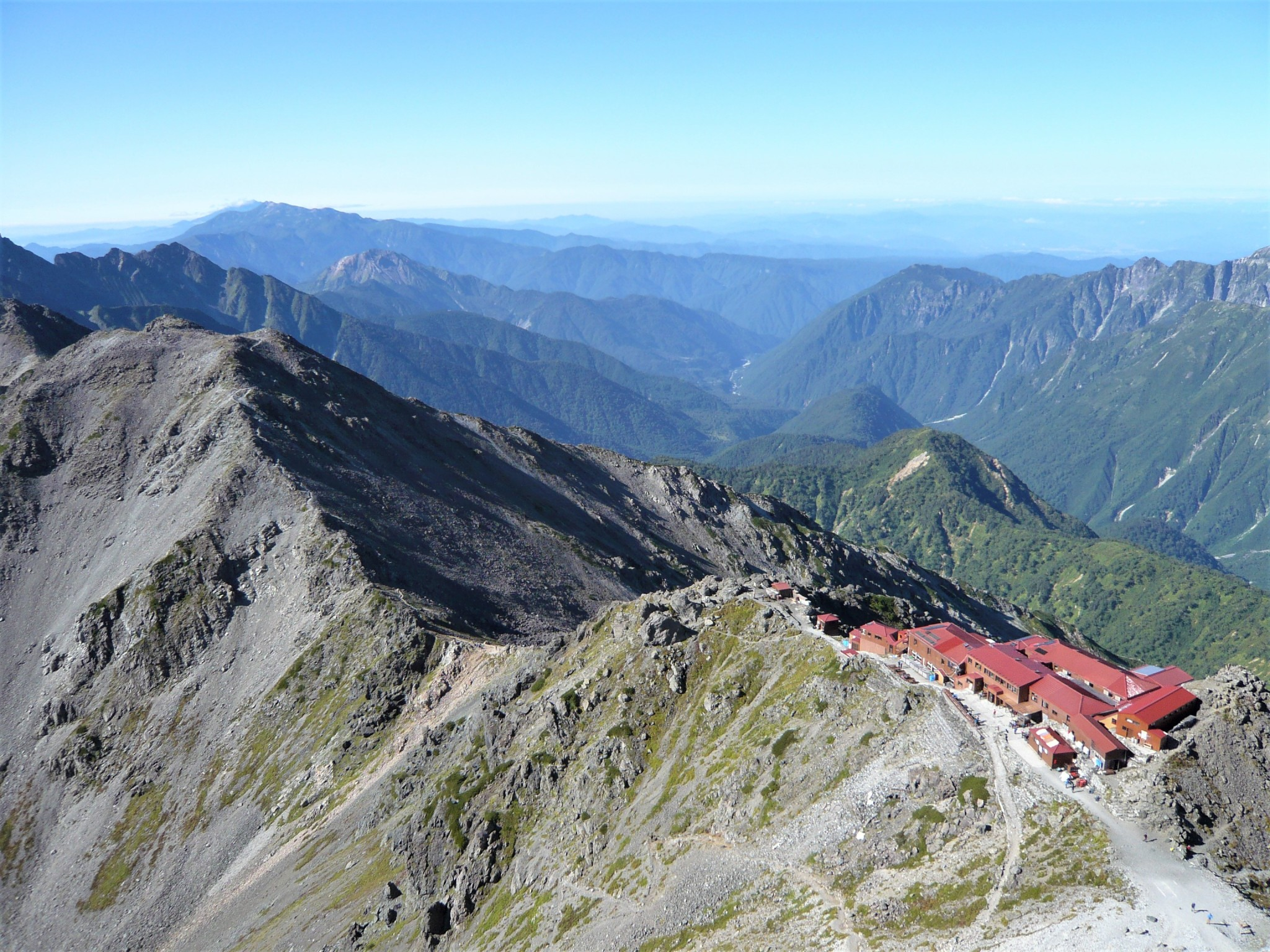 A small collection of buildings perched precariously on a dramatic mountain ridgeline with other peaks visible in the distance.