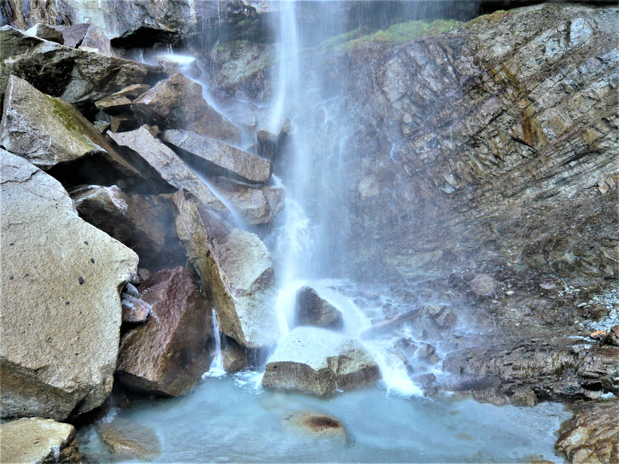 A turbulent waterfall cascading over large rocks and boulders into a clear pool of water at Mount Houou in Japan.