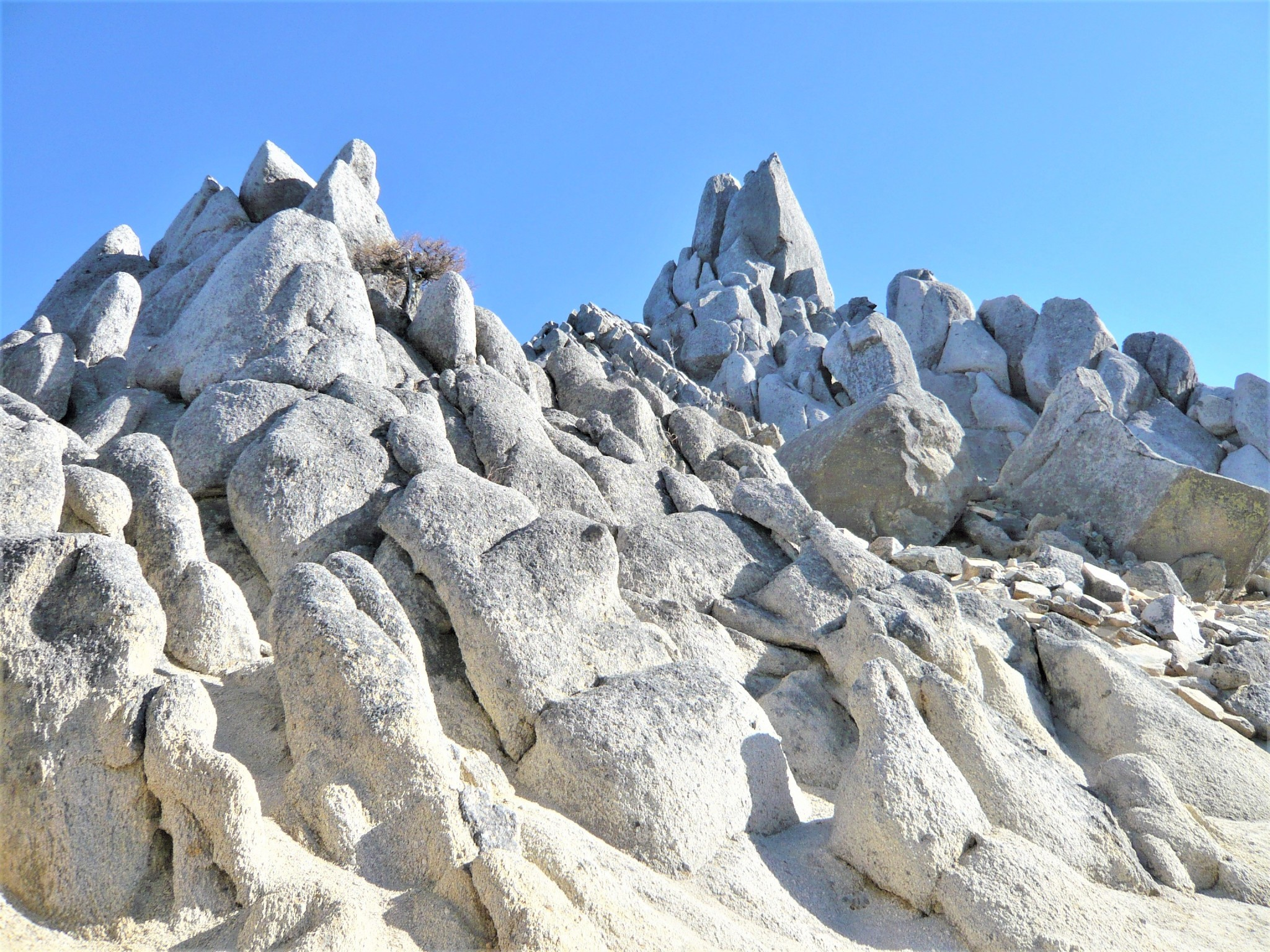 The surreal rock formations of Mount Jizo set against a clear blue sky in the Japan Alps.