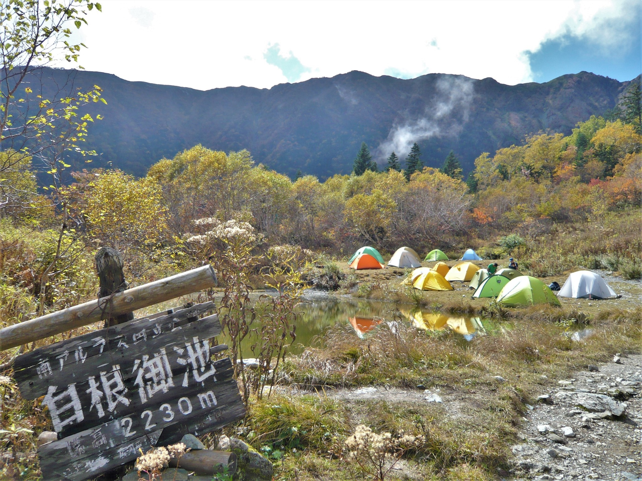 Colourful tents next to a calm pond surrounded by trees and mountains at an idyllic campsite in the Japan Alps.