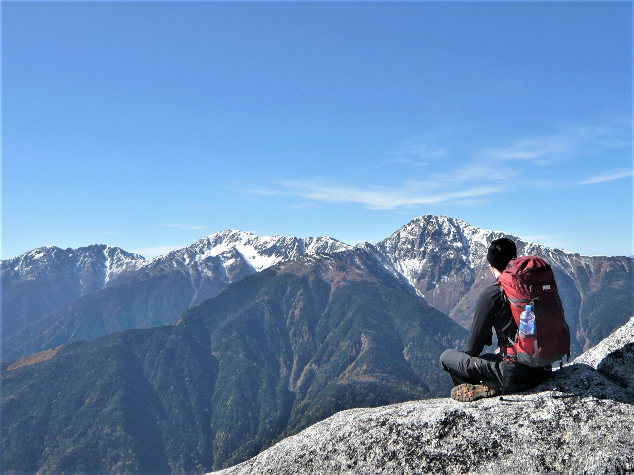 A sitting hiker gazing out over a collection of snow-covered peaks in the Japan Alps.