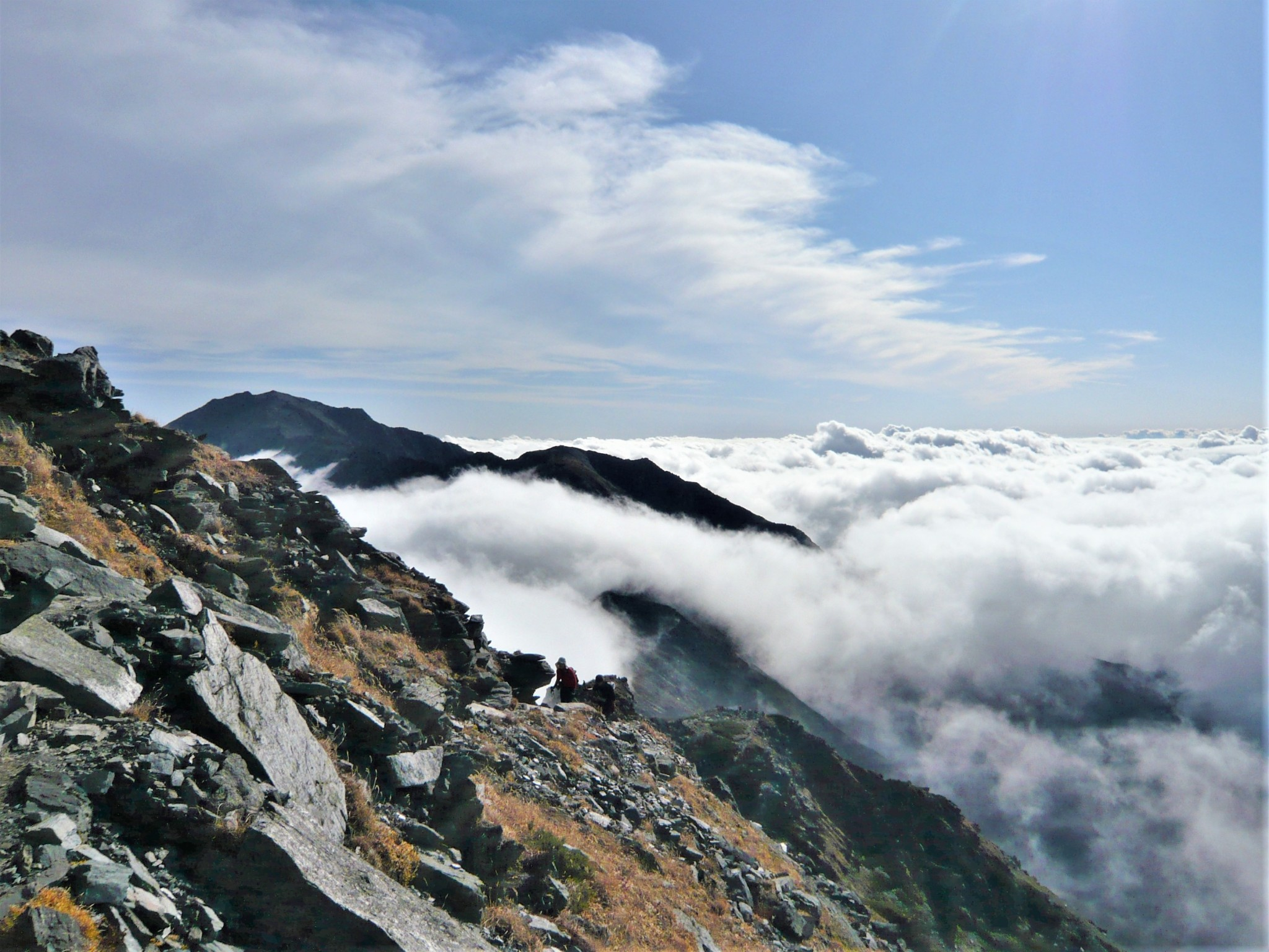A rocky mountain ridgeline rising out of and above a sea of white clouds in the Japan Alps.