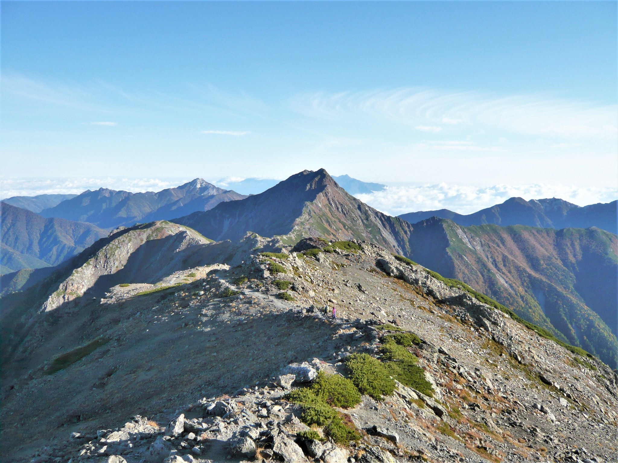 The ridgeline and summit of Mount Kita on a clear morning as seen from the summit of Mount Aino in the Japan Alps.