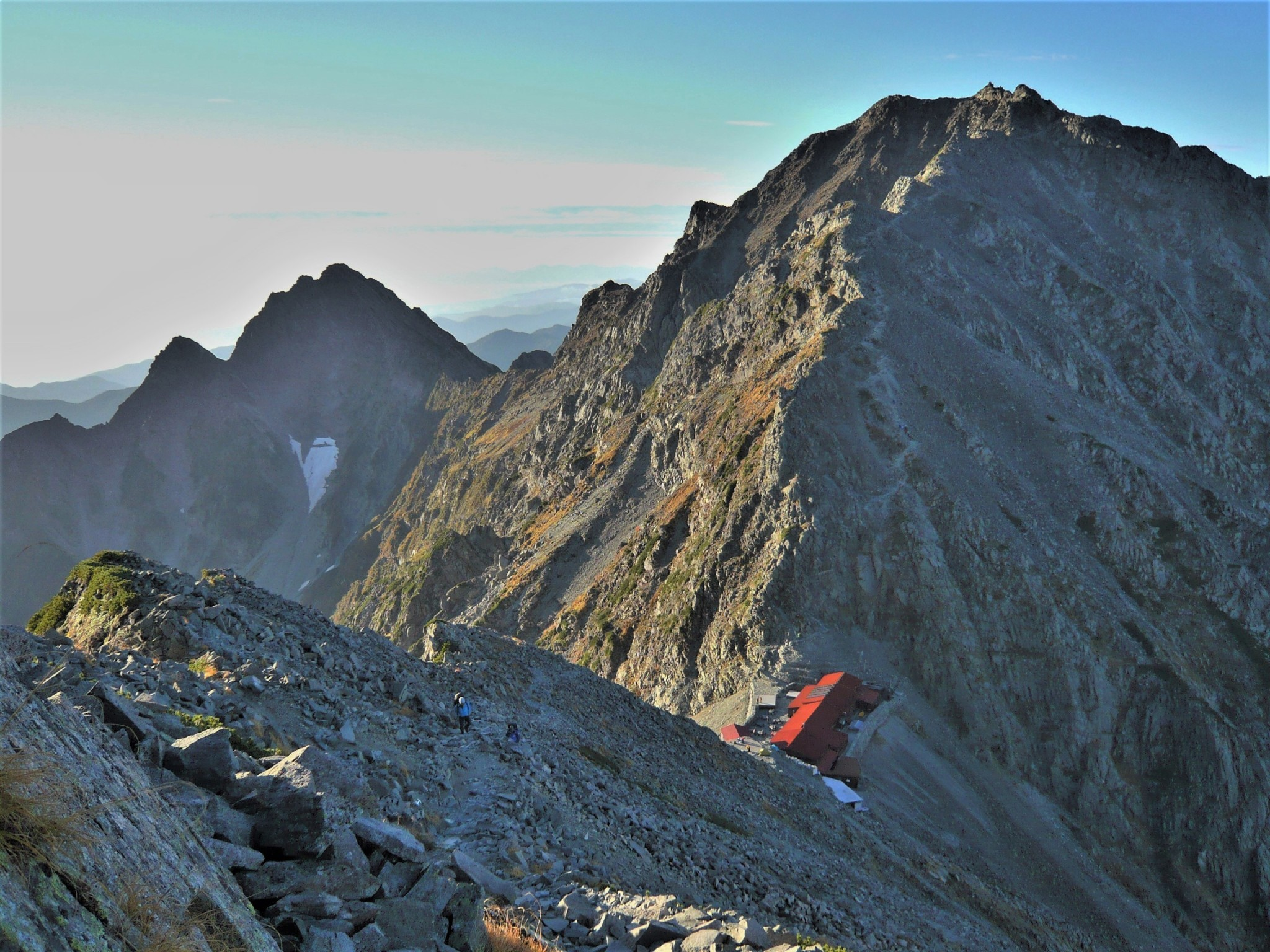 A small mountain lodge perched precariously on a dramatic mountain ridgeline between Mount Oku Hotaka and Mount Karasawa in the Japan Alps.