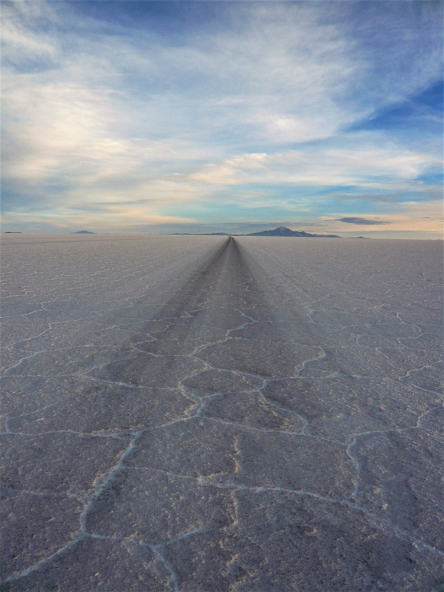 A path leading over the white salt flats of the Salar de Uyuni in Bolivia towards the horizon and a blue sky.