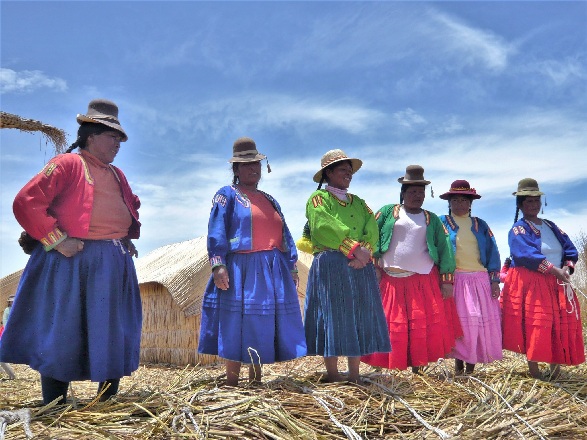A group of Peruvian women in colourful traditional dress standing on an island of reeds.