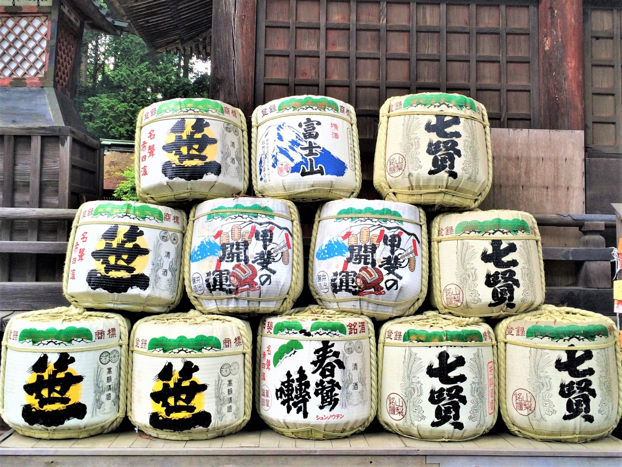 A stack of traditional Japanese sake casks in front of a wooden temple.