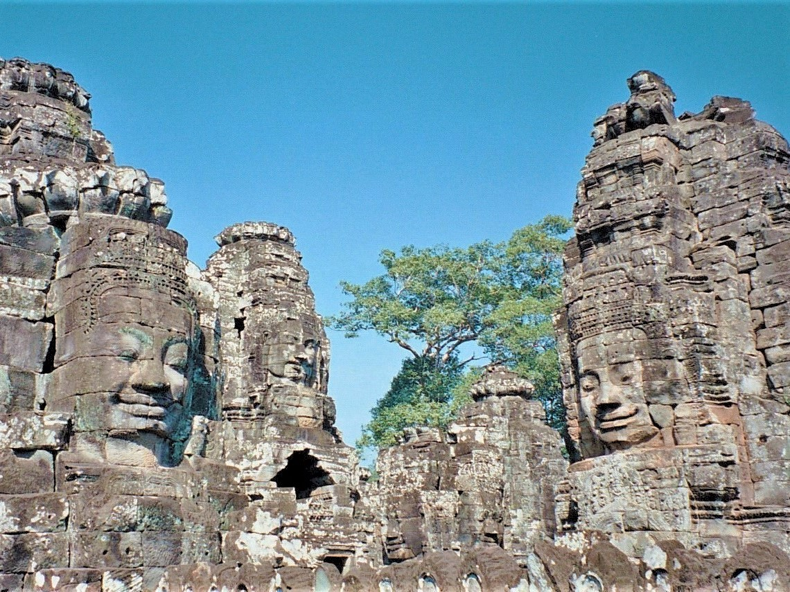 An ancient Khmer temple at Angkor in Cambodia, featuring several stone heads in front of a blue sky.