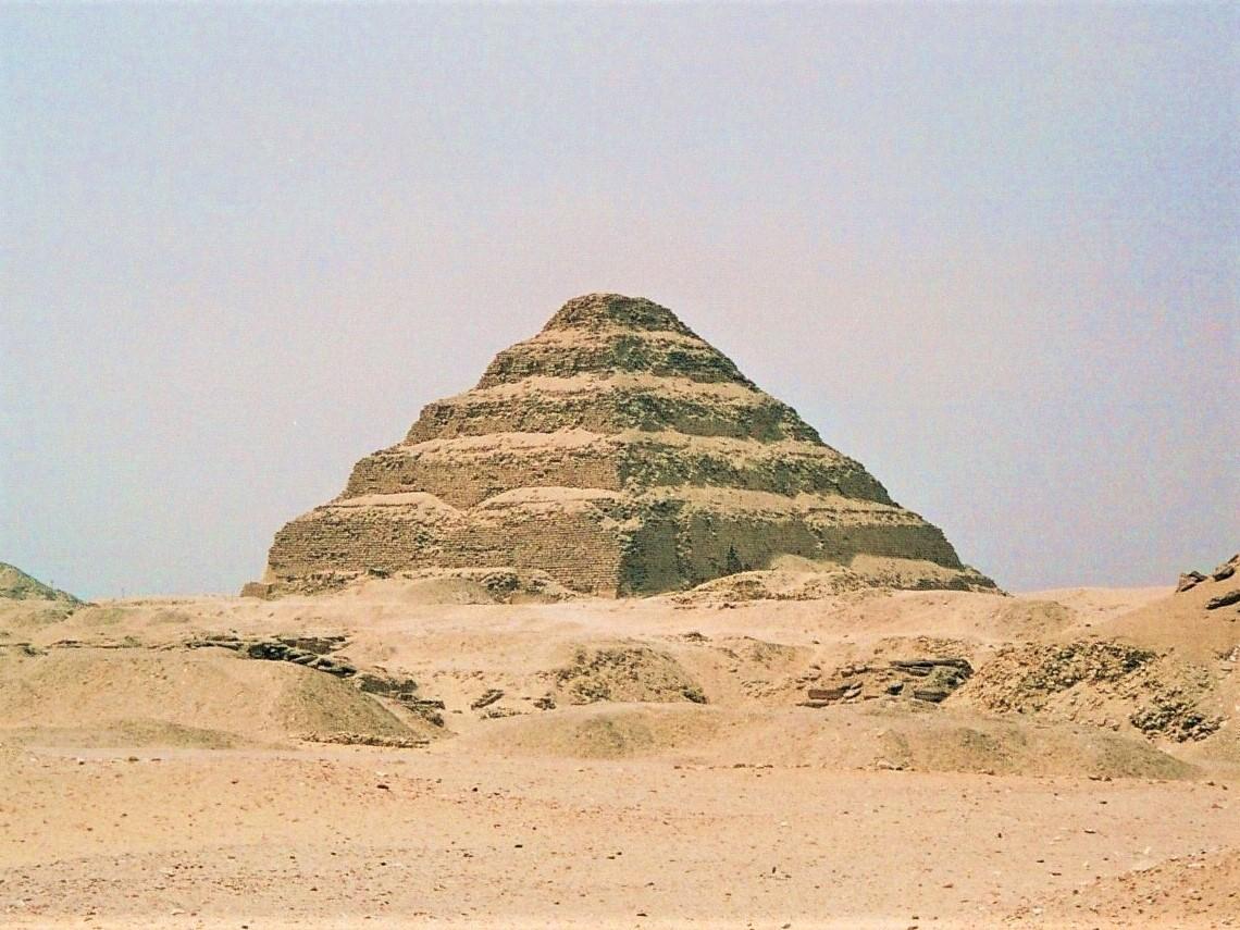 Djoser's ancient Egyptian step pyramid and surrounding sandy landscape at Saqqara.